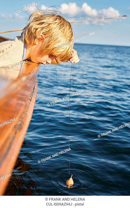 Boy dangling fishing float from boat