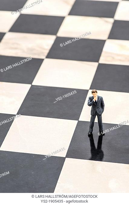 Small figurine of businessman standing on chessboard and thinking of strategic planning