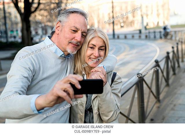 Senior couple taking selfie with smartphone on sidewalk in city