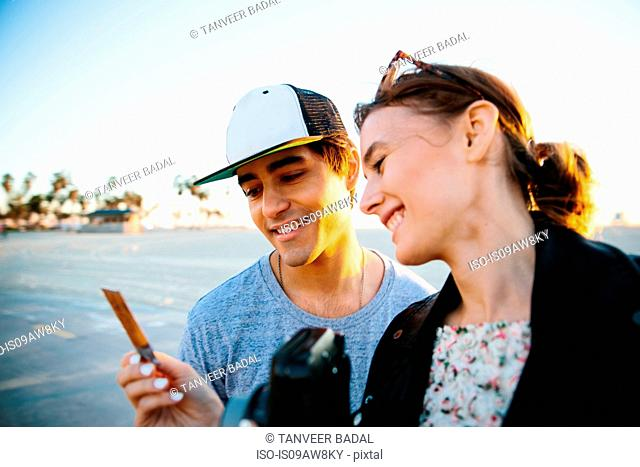 Young couple looking at instant photograph at coast, Venice Beach, California, USA