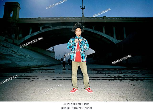 Asian man standing under overpass