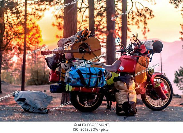 Part unloaded touring motorcycle parked on forest roadside at sunset, Yosemite National Park, California, USA