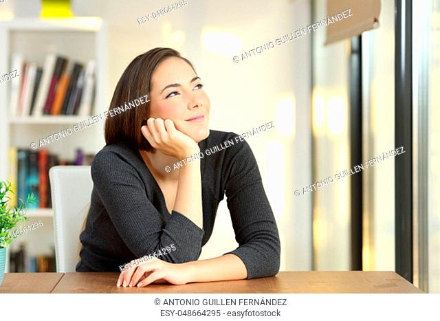 Satisfied homeowner thinking or draeming looking above sitting in a table at home
