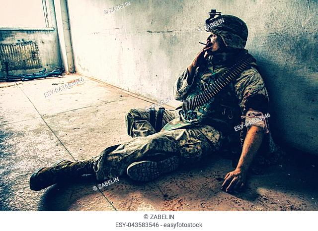 Soldier in combat uniform and ammo belt over chest, sitting on floor and smoking after being shoot in shoulder and put bandage on wounded hand