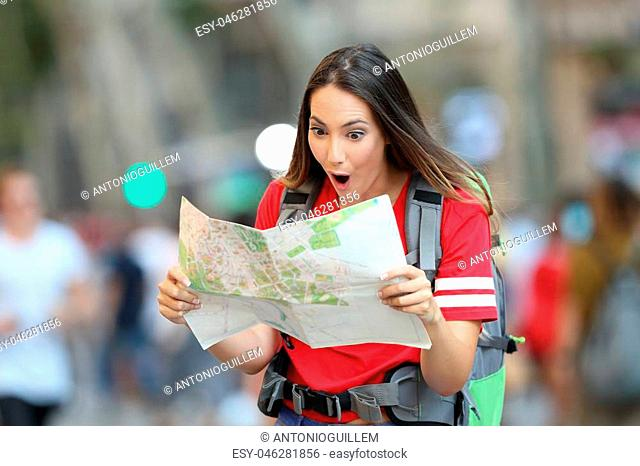 Surprised teen tourist reading a paper guide walking on the street