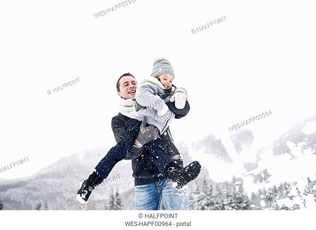 Father playing with daughter in winter landscape