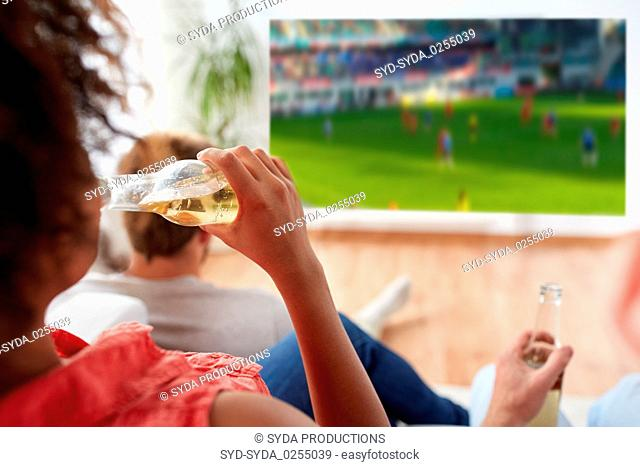 woman drinking beer and watching soccer game