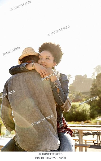 Couple hugging on picnic table in park