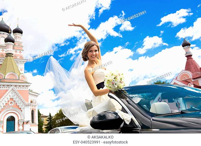 Beautiful young happy bride sitting in cabriolet