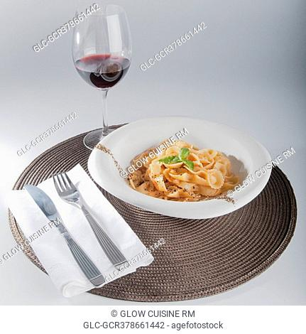 Close-up of pepper and basil garnished pasta with red wine