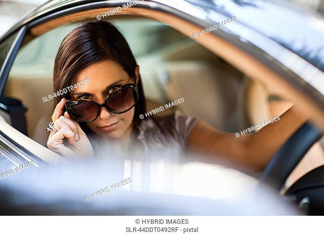 Woman peering over sunglasses in car