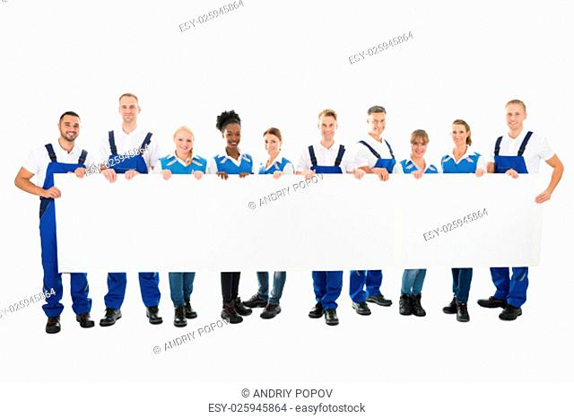 Portrait of happy multiethnic janitors holding blank billboard against white background
