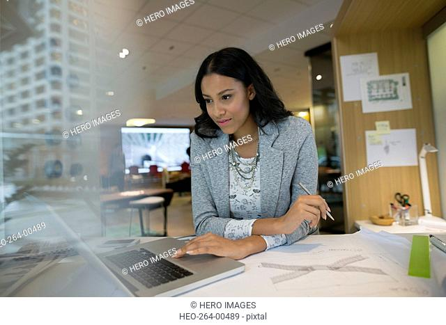 Young female architect using laptop at office desk
