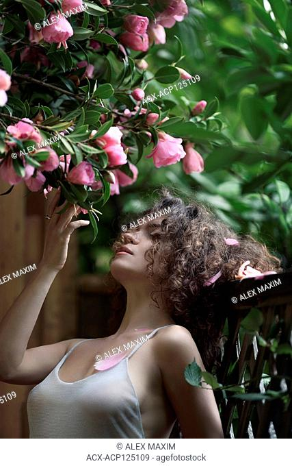 Artistic sensual portrait of a young beautiful woman standing outdoors by the garden fence under a blooming camellia tree touching its pink flowers