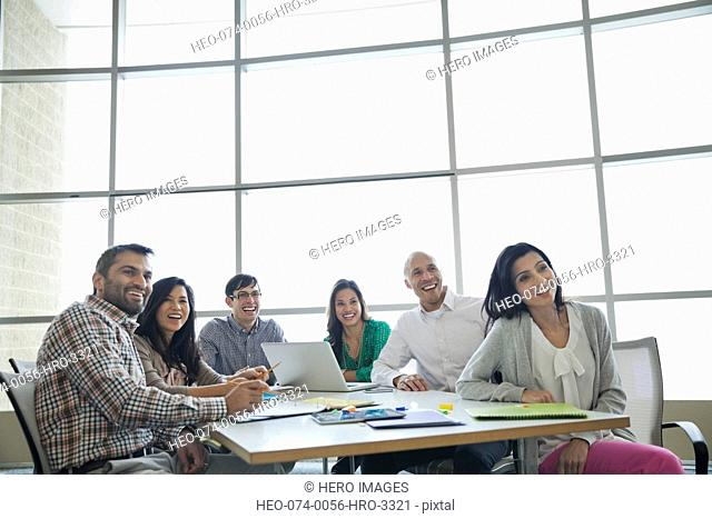 Smiling business team looking away in conference room