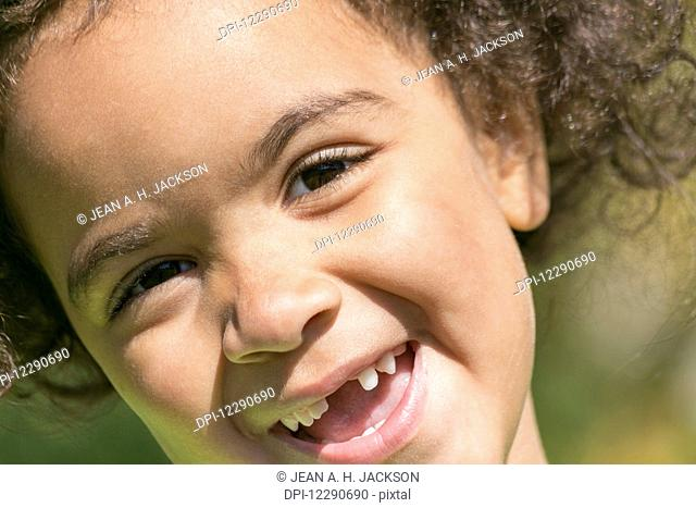 Close up portrait of a young girl with teeth missing in her smile; Edmonton, Alberta, Canada