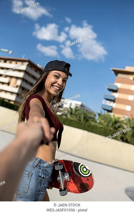 Young woman in skate park, holding hand of a man