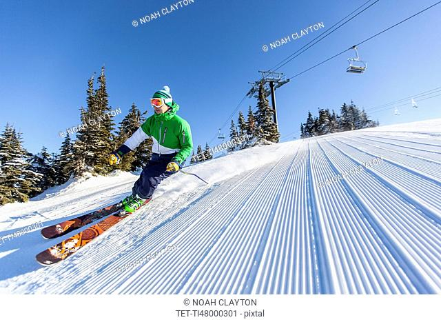 Mature man on ski slope under blue sky