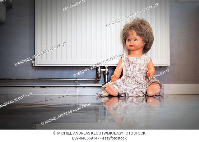 Abandoned doll sitting on a concrete floor