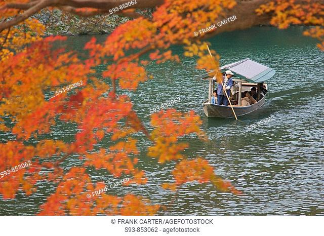 A pleasure boat framed in red-ornge maple leaves being poled along the pond in Arashiyama