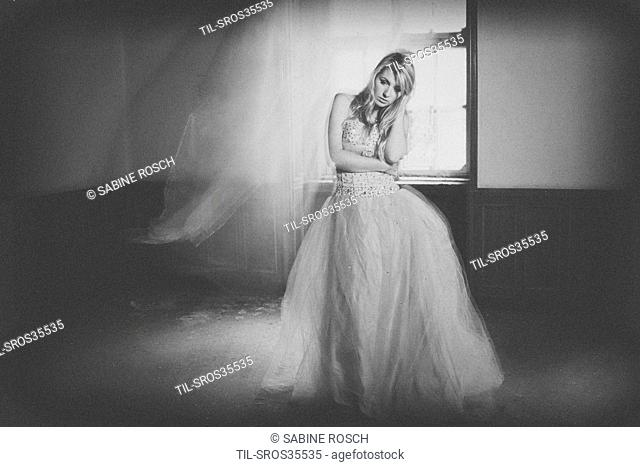 Young lady with blonde hair in a vintage dress standing in an old room