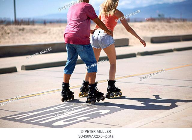 Couple rollerblading outdoors, man holding woman's waist, rear view