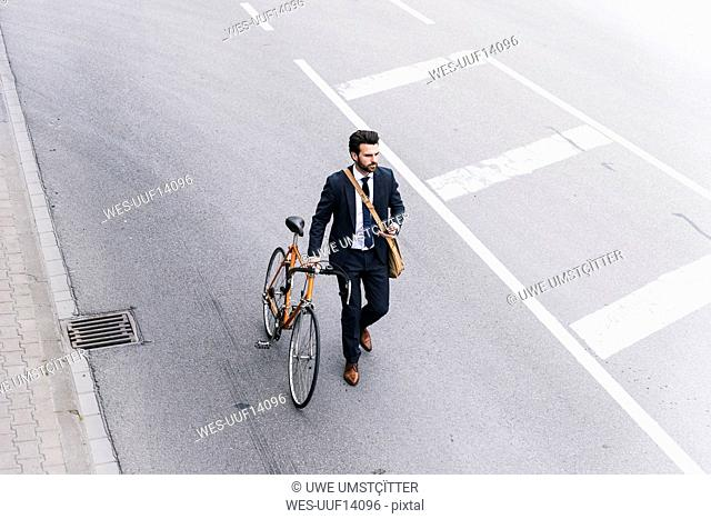 Businessman with bicycle and cell phone walking on the street