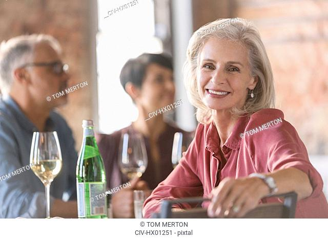 Portrait smiling senior woman dining with friends in restaurant