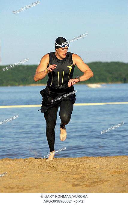 A male athelete running out of the water while training for a triathlon