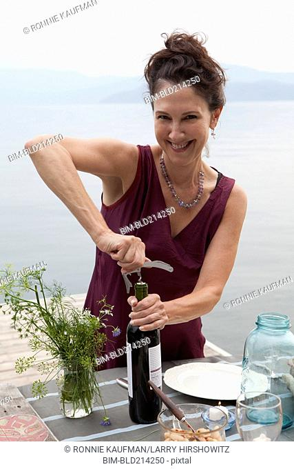 Caucasian woman opening wine bottle at table near lake