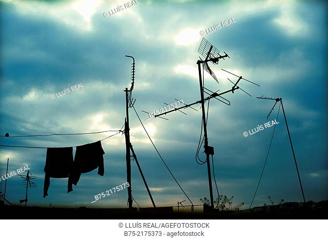 Backlit television antennas and hanging clothes and in the background, sky with clouds, in the Medina of Fez, Morocco, Africa