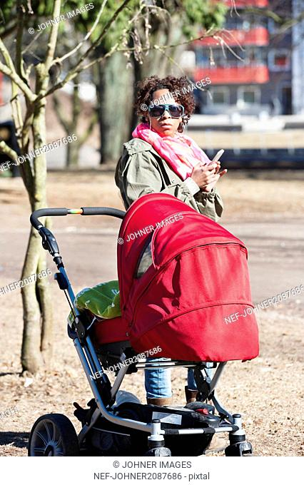Woman with cell phone and pram