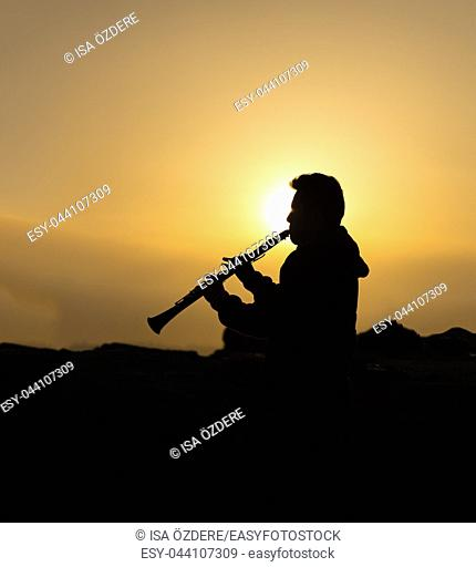 An unidentified man plays clarinet at sunset on the beach in Istanbul,Turkey. 18 April 2015