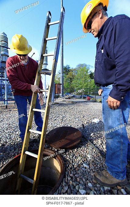 Power engineers placing ladder inside manhole at high voltage power distribution station, Braintree, Massachusetts, USA