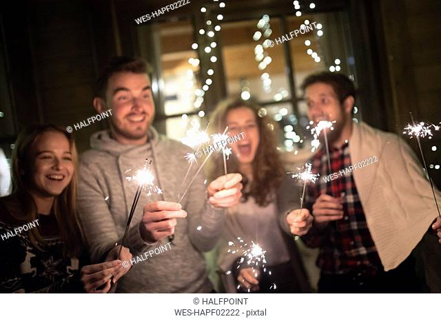 Happy friends holding sparklers outdoors at night