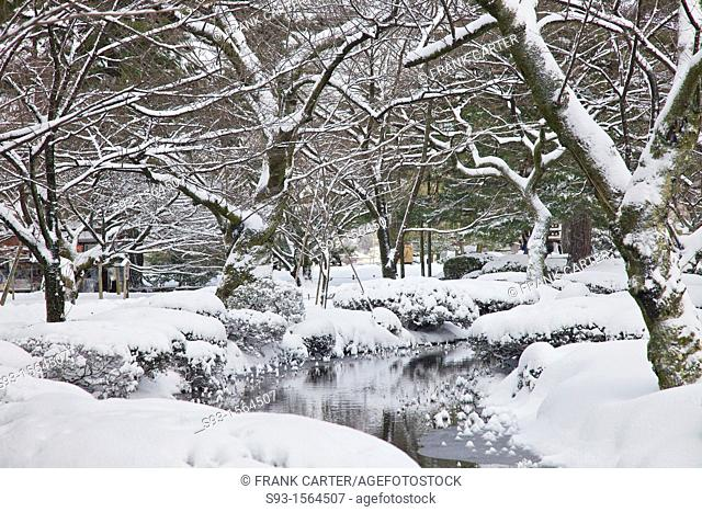 A small stream running through a part of a snow covered Kenrokuen Garden