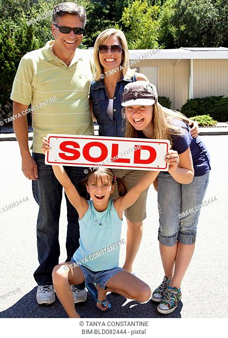 Excited Caucasian family holding sold sign