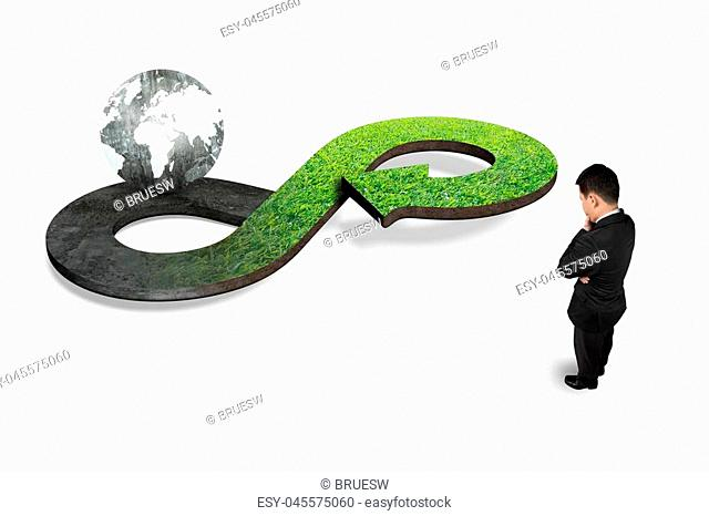 Green circular economy concept. Man looking at arrow infinity symbol with grass texture and black white globe, isolated on white