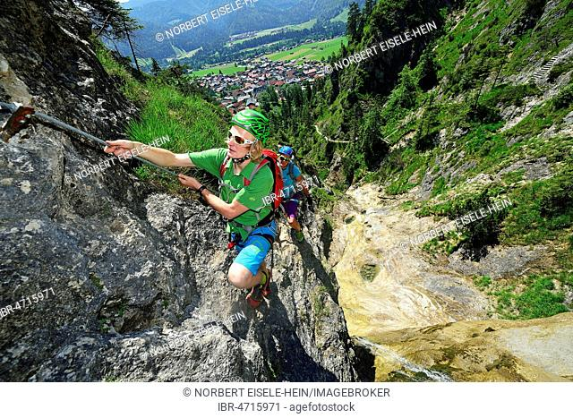 Climbers at rock face, via ferrata Hausbachfall, Reit im Winkl, Chiemgau, Bavaria, Germany