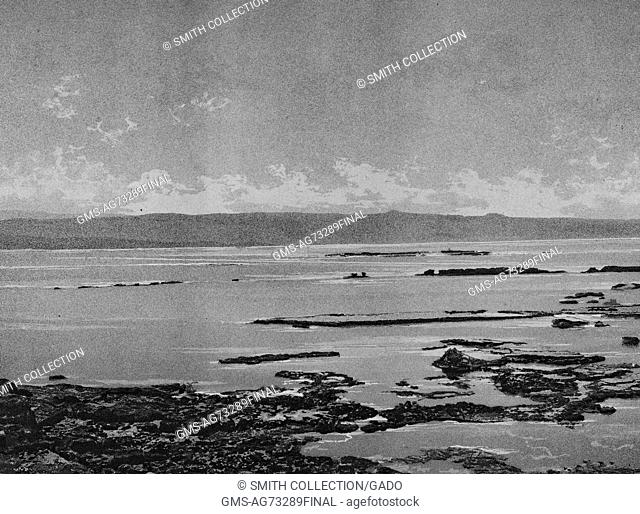 Black and white photograph of a rocky shoreline, clouds and land mass in the background, captioned 'Tyr, brise-lames du Port Egyptien', Tyre, Lebanon, 1874