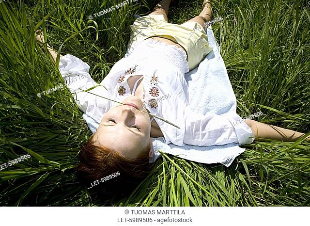 Woman lyeing on grass in the meadow in summer