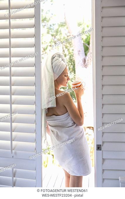 Young woman wrapped in a towel holding cup of coffee