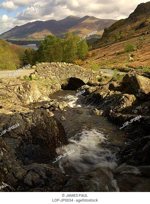 England, Cumbria, Keswick, Ashness Bridge with views of the peaks of Skiddaw in the distance