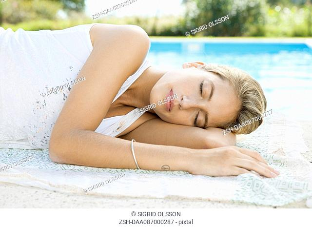 Woman resting at poolside with eyes closed