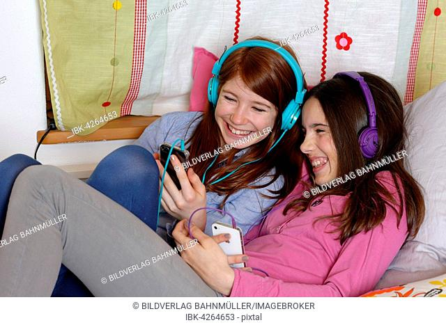 Girls, friends listening to music together with headphones, Upper Bavaria, Germany