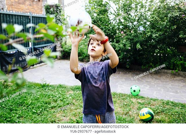 child plays ball in the garden of the house