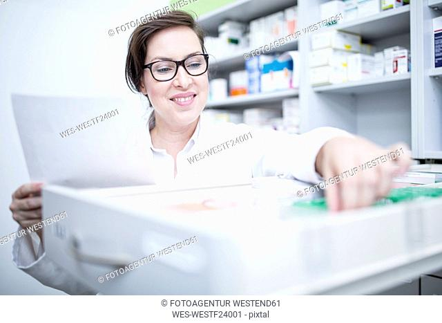 Smiling pharmacist seeking out medicine at cabinet in pharmacy