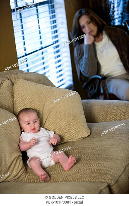 Mother suffering from postpartum depression, sitting by a window while the baby lies on a sofa