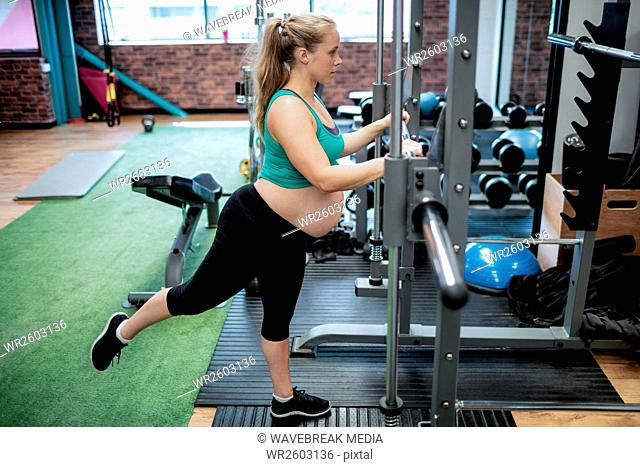 Pregnant woman exercising with fitness bar