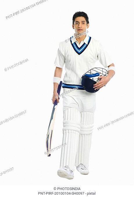 Cricket batsman carrying a bat and a helmet